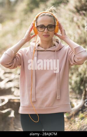 Ritratto di bella donna sportiva che indossa occhiali da sole, felpa con cappuccio e cuffie durante la sessione di allenamento all'aperto