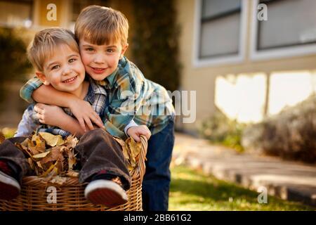 Due giovani fratelli in gioco abbracciano un fresco giorno di caduta. Foto Stock