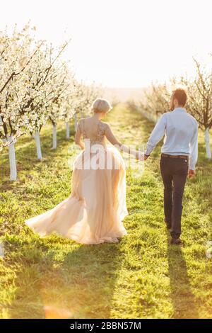 Retro vista a tutta lunghezza di romantica coppia uomo e donna in primavera giardino fiorito, tenendo le mani e camminando insieme tra file di alberi in fiore Foto Stock