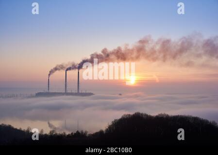 Fotografia orizzontale di tre pile fumanti di centrale termica all'orizzonte prese dalla collina, tubi sono in nebbia serale su cielo blu, copia spazio. Concetto di inquinamento ambientale