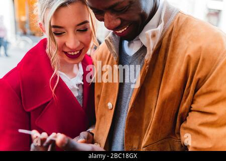 Sorridente giovane coppia che condivide il cellulare Foto Stock