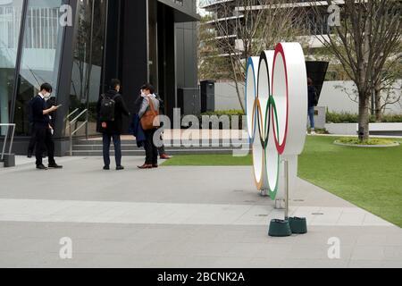 Persone fuori dal Museo Olimpico del Giappone vicino a un monumento agli anelli Olimpici. Indossano maschere facciali durante l'epidemia di coronavirus.
