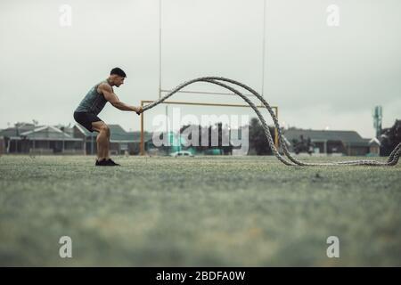 Uomo di fitness che utilizza corde di allenamento per l'esercizio all'aperto a terra. Atleta che si sta lavorando con corde di battaglia all'aperto.