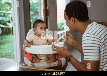 padre che alimenta il bambino. pasto tempo uomo che prende cura di sua figlia