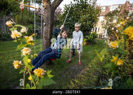 Due giovani fratelli di 6 e 9 anni che giocano su una scala di corda e swing di corda nel loro giardino posteriore, Londra, Inghilterra, Regno Unito Foto Stock