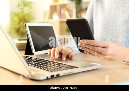 Primo piano delle mani di una donna utilizzando più dispositivi seduti su una scrivania a casa