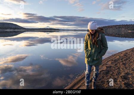 Giovane donna che cammina lungo il lago al tramonto con la montagna sullo sfondo Foto Stock