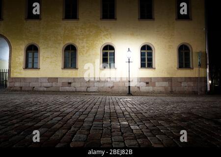 Strada vuota di notte alla luce di una lampada da strada di vecchio stile.
