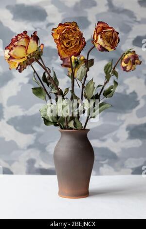 Bouquet di rose multicolore appassite in vaso di ceramica marrone. Sfondo grigio parete.
