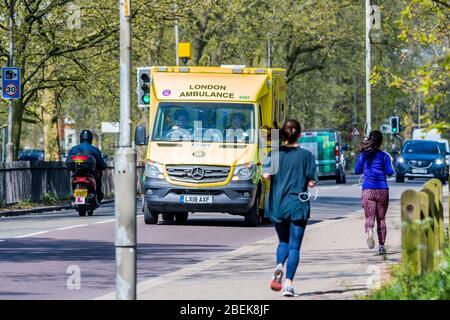 Londra, Regno Unito. 14 Aprile 2020. I joggers passano un'ambulanza sulla circolare sud - Clapham Common è abbastanza tranquillo. Il blocco continua per l'epidemia di Coronavirus (Covid 19) a Londra. Credit: Guy Bell/Alamy Live News