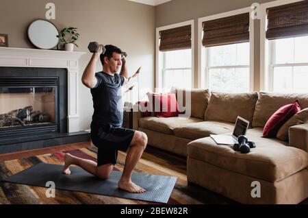 Uomo che lavora con i pesi a casa utilizzando il programma di esercizio online.