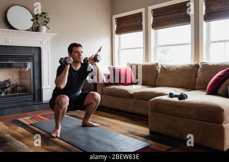 Uomo in forma che esercita a casa con pesi delle mani nel suo soggiorno.