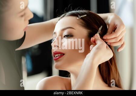 messa a fuoco selettiva del make up artista che tocca clip capelli su modello attraente