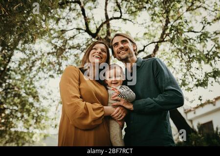 Bella coppia sorridente che posa in giardino con il figlio in braccio. Foto Stock