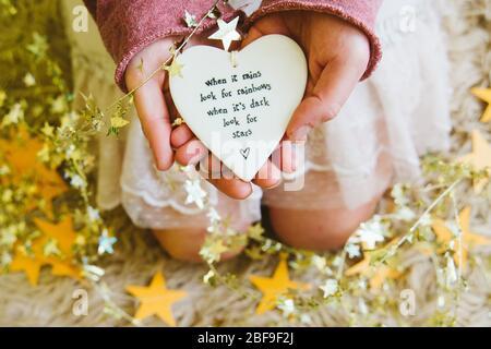 Una ragazza o una donna che tiene un cuore con la citazione quando piove cercare arcobaleni, circondato da stelle d'oro. Blocco del coronavirus positivo sollevamento