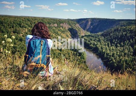Giovane donna felice con uno zaino siede su una scogliera e guarda la valle sottostante