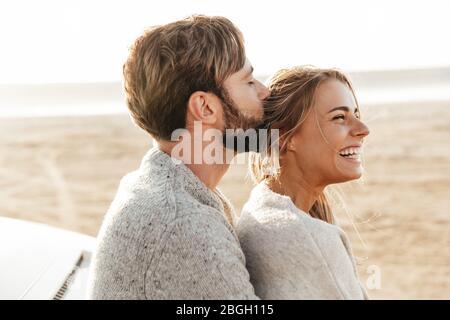 Primo piano di una giovane coppia felice innamorata abbracciando mentre si appoggia su una macchina alla spiaggia soleggiata, baciando