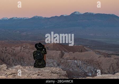 Donna guardando il sole tramontare sulle Ande Montagne dalla Valle della Luna, Atacama deserto, Cile Foto Stock