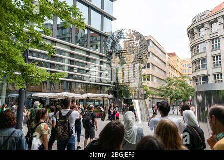 Persone, turisti che guardano la testa di Franz Kafka conosciuta come la statua di Kafka scultura all'aperto di David Cerny, installato fuori del Quadrio shopping