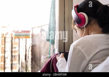 bambina seduta di fronte al suo balcone di casa con cuffie guardare video sul telefono, home entertainment per bambini concept, copia spazio per t Foto Stock