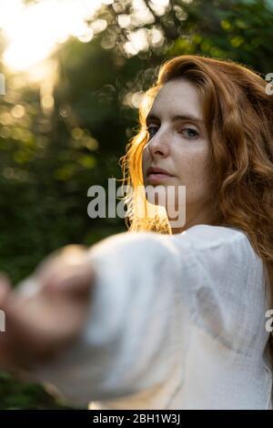 Giovane donna dai capelli rossi che le tira fuori le mani nella foresta