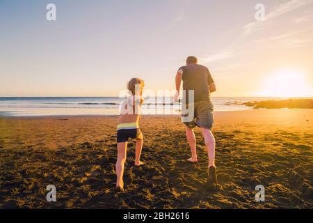 Padre e figlio in esecuzione sulla spiaggia, vista posteriore Foto Stock