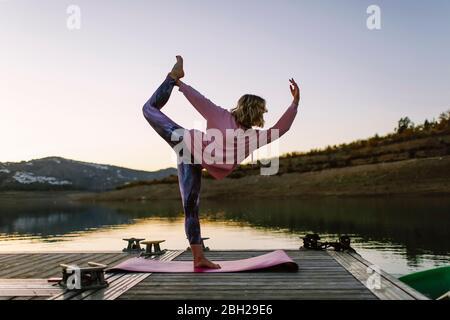 Giovane donna che fa yoga su un molo, posizione ballerina