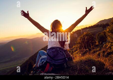 Giovane donna alzarsi mano su in cima alla montagna e tramonto cielo sfondo astratto.