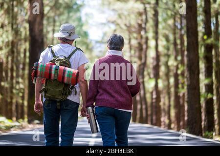 Un paio di anziani camminano nel mezzo di una strada con foresta e zaino con coperta sul retro. Amore per sempre partnersip e naturale concetto di stile di vita libero senza limiti di età