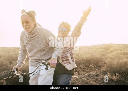 Felicità e libertà concetto senza limiti età con la coppia di vecchi anni ridendo sorridendo e avendo molto divertimento insieme su una bicicletta in attività di svago all'aperto - giovani e giocosi pensionati