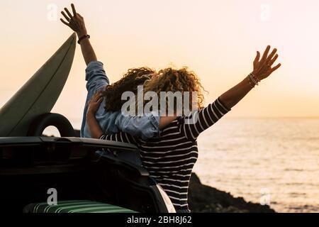 Felice coppia di ragazza ricci divertirsi insieme e guardare il tramonto di fronte all'oceano in vacanza tropicale bella all'aperto - abbraccio e amicizia per le persone felici