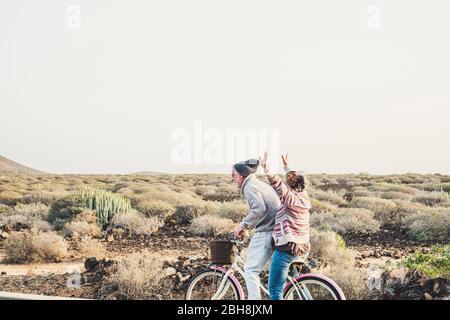 Coppia matura e di età caucasica hanno un sacco di divertimento a cavallo insieme la stessa bicicletta in attività di svago all'aperto felice insieme in relazione e per sempre concetto - godere di stile di vita e non terminare mai la felicità