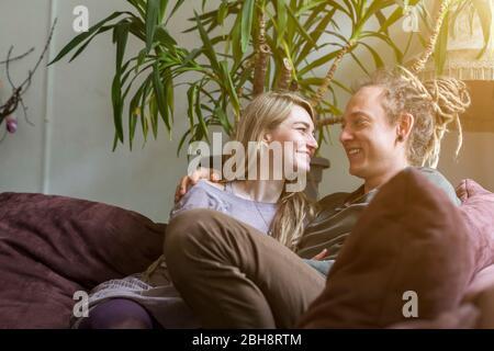 Amorevole giovane coppia felice e moderna con i Dreadlocks seduta braccio in braccio su un divano ridendo e guardando gli altri occhi