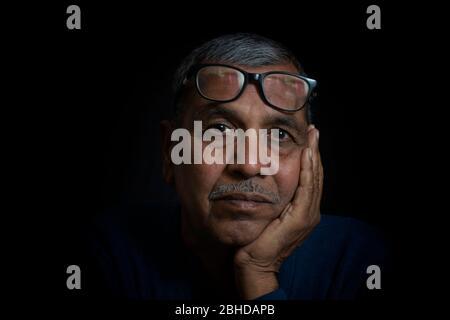 Primo piano ritratto di pensiero senior uomo su sfondo nero Foto Stock