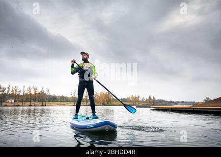 Atleta in neoprene paddleboard ad esplorare il lago a freddo contro il cielo nuvoloso Foto Stock