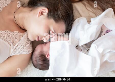 maternità, infanzia, infanzia, famiglia, cura, medicina, sonno, salute, maternità concetto - ritratto di mamma con neonato avvolto in pannolino su Foto Stock