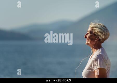 Donna anziana jogging all'alba. Mattina che corre sullo sfondo il mare e le montagne