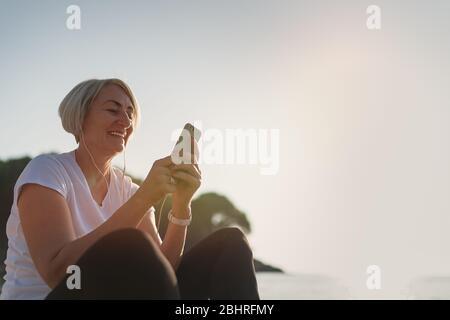 Donna matura seduta dopo jogging sulla spiaggia. Signora senior che usa smartphone e auricolari al tramonto. Corsa serale