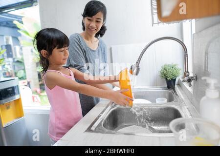 Aiuto mano. Cute Little Girl aiuta la sua madre nel lavare i piatti alla cucina familiare Foto Stock