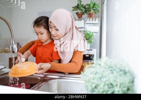 Aiuto mano. Cute Little Girl aiuta la sua madre musulmana nel lavare i piatti alla cucina di famiglia Foto Stock