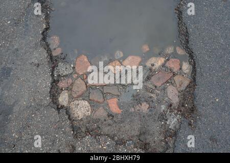 Buco del vaso rivelando vecchia strada di pietra sotto asfalto moderno.