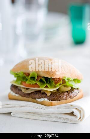 Cheeseburger con insalata e pomodoro su panino di ciabatta su tovagliolo bianco -