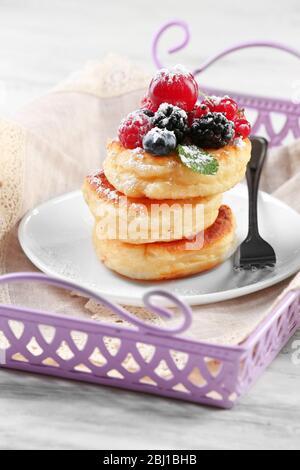 Frittelle di formaggio casolare con frutti di bosco in piatto, primo piano Foto Stock