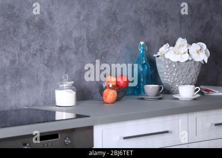 Ciotola di vetro con mele, tazze di caffè e fiori di orchidee bella nel vaso sul tavolo da cucina, primo piano