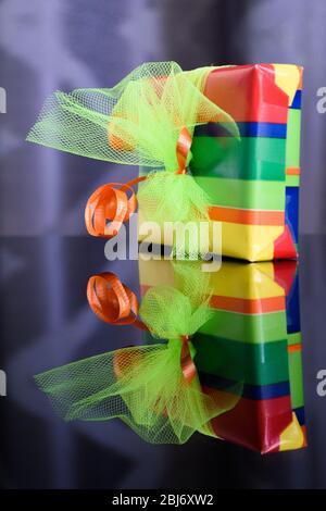 Scatola regalo luminosa e colorata riflessa nel tavolo di vetro sottostante