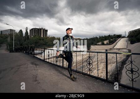 Uomo con barba grigia in costume nero e zainetto in esecuzione sul ponte che attraversa il fiume sporco a sfondo con cielo nuvoloso