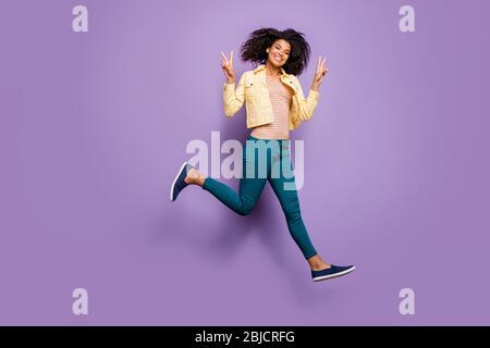 Girata foto di dimensioni del corpo di allegra toothy ragazza che si infuocava in pantaloni pantaloni camicia gialla junping esecuzione mostrando v-segno isolato pastello Foto Stock