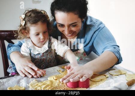 Madre e figlia che cuoce i biscotti in cucina - pasta sfoglia con taglierine in plastica Foto Stock