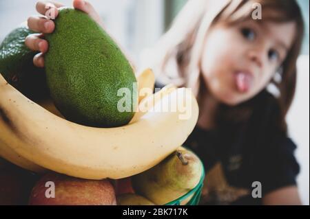Mano della bambina prendendo un avocado da un cesto di frutta. Mano del bambino che tiene avocado fresco verde maturo. Cibo sano per i bambini. Faccia divertente di piccolo gir Foto Stock