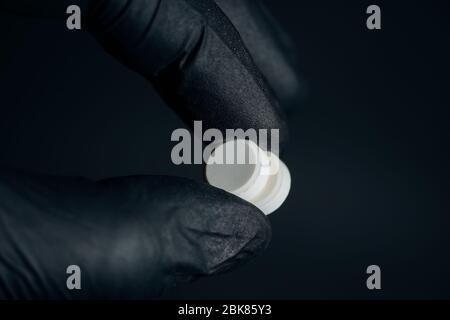 Tenere in mano pillole gialle con guanti da vicino su sfondo scuro Foto Stock